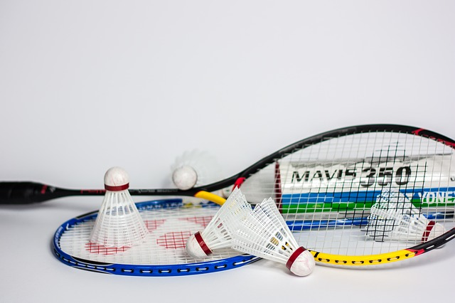 Shuttlecocks resting on a badminton racket.