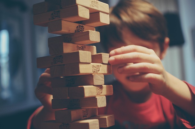 A kid is playing with jenga tiles.