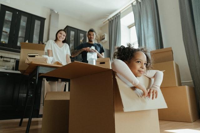 A kid in a card box in home.