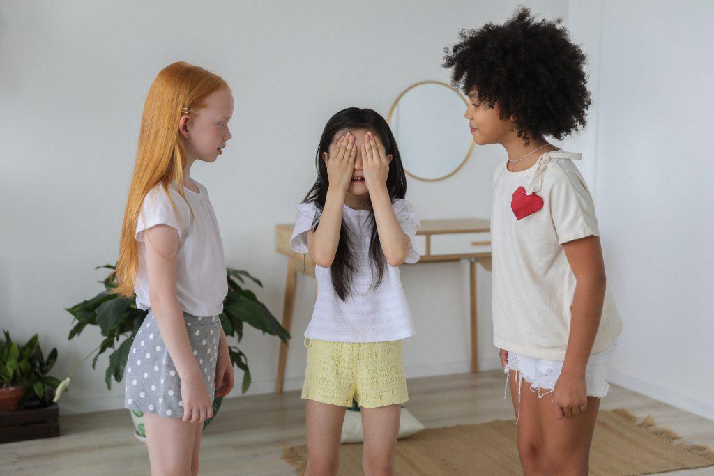 Three kids playing hide and seek.