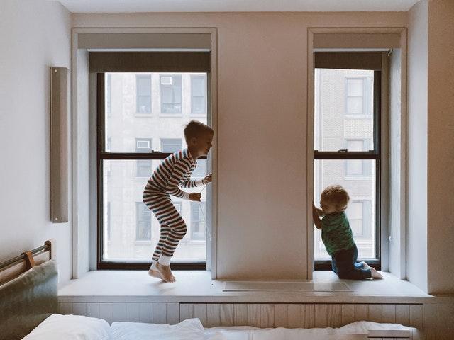 Two kids p[laying beside glass windows.