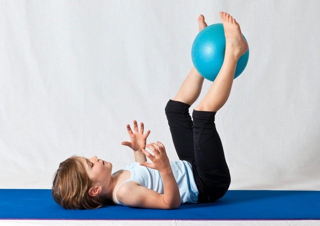 A kid is playing with a blue exercise ball.