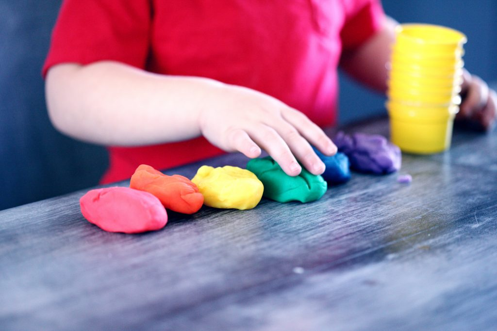 A kid is making figures out of play dough.