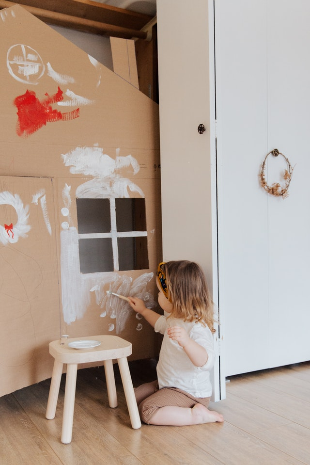 A kid is painting a home made out of card box.